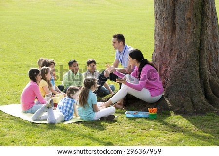 Small group of children sitting on the grass having a lesson outdoors. Male and female teacher can be seen. The children look to be listening and enjoying themselves.  - stock photo