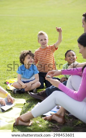 Small group of children sitting on the grass having a lesson outdoors. Only side of the teacher can be seen. The children look to be listening and enjoying themselves.