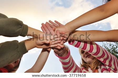 Small group of happy children outdoor, their hands
