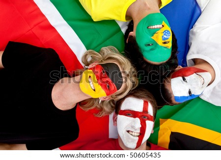 Small group of happy international football fans lying on the floor - stock photo