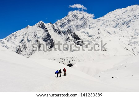 Small group of mountain trekkers in high winter Himalayas mountains, Nepal - stock photo