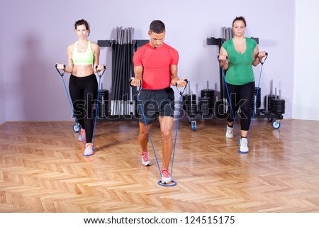 Small group of people doing bicep exercise using resistance bands - stock photo