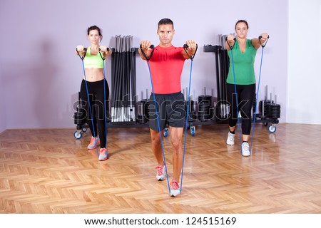 Small group of people doing shoulder exercise using resistance bands