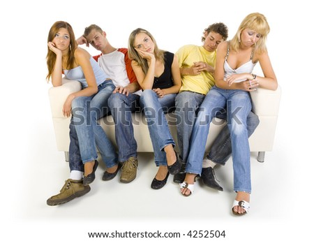Small group of sad teenagers sitting on couch. One girl is looking at watch. White background, front view - stock photo