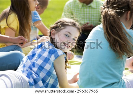 Small group of school children having a class outdoors. A girl turns her head to look behind into the camera and smiles. - stock photo