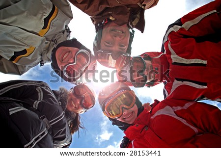 Small group of  snowboarders standing in huddle, smiling, low ange view. - stock photo
