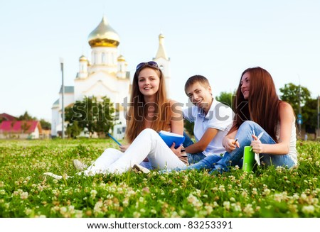 small group of students in a clearing in  background of church - stock photo