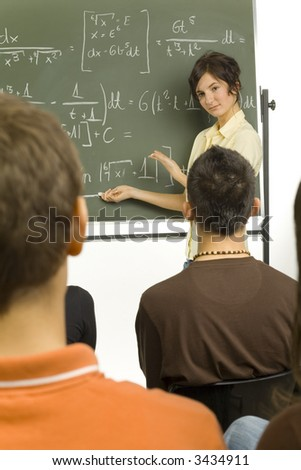 Small group of teenagers sitting in front of blackboard. One girl standing  beside the blackboard and showing something to the rest - stock photo