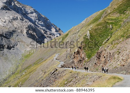 Small group of the tourists are hiking on the asphalt road along the slope of green mountain Col de Tentes. - stock photo
