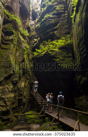 Small group of tourists walking wooden path which runs among high sandstone cliffs. Creative long time exposed landscape photography illuminated by backlight from direction of space between rocks. - stock photo