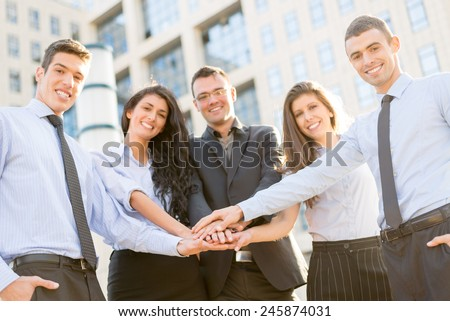 Small group of young business people standing in front of the company with folded hands, motivating for new business wins. With a smile, looking at the camera. - stock photo