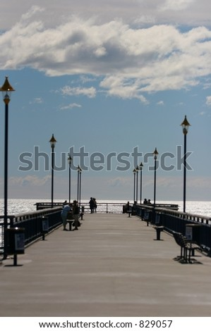 Small groups of people out for a walk on Brighton pier, in Christchurch, New Zealand.  Sea at Horizon is in focus, everything else is soft. - stock photo