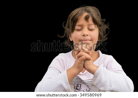 Small gypsy child praying with folded hands having devotional time, isolated on black background