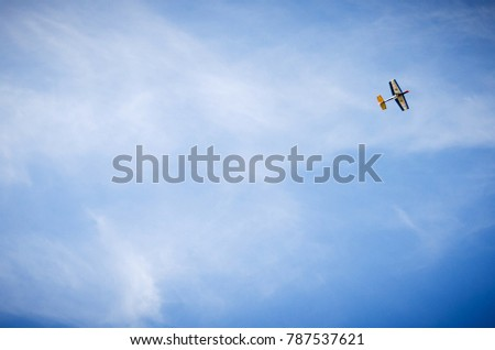 small hand-crafted wooden plane against a blue sky with white clouds
