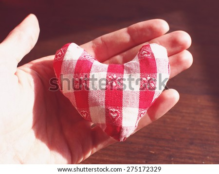 Small handmade heart in a hand with brown wooden table in the background - stock photo