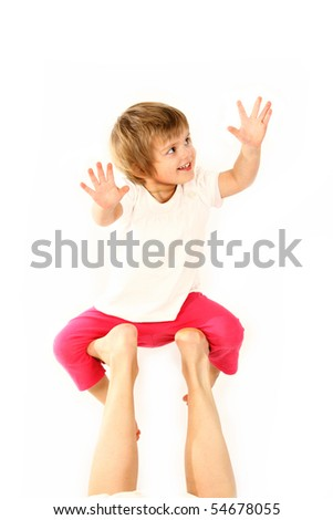 small happy baby girl is playing with moms legs - stock photo