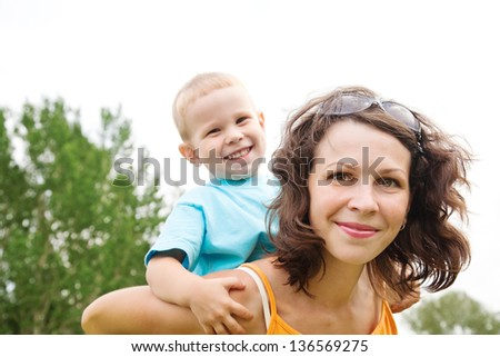 Small happy boy enjoying a piggyback ride on his mothers back - stock photo