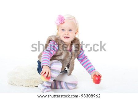 small happy girl in a fur vest on a white background. Studio shooting