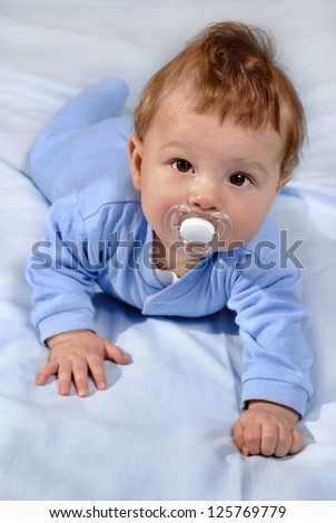 small healthy baby on a bed of blue color - stock photo