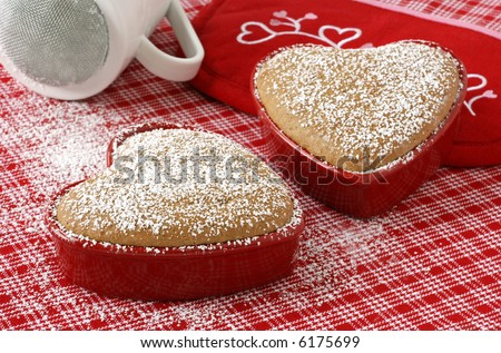 Small, heart shaped spice cakes fresh from the oven with powdered sugar sprinkled all around.  Close-up with soft, natural lighting and shallow dof. - stock photo