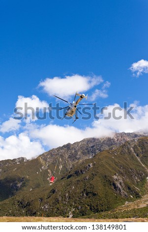 Small helicopter with transport cargo bucket flying in blue sky over mountains of Southern Alps  New Zealand  to supply remote site - stock photo