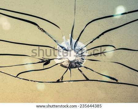 small hole of bullet impacting through transparent glass - stock photo