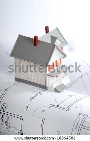 Small home model on a set of blueprints; shallow depth of field - stock photo