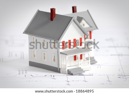 Small home on top of mechanical drawings - stock photo