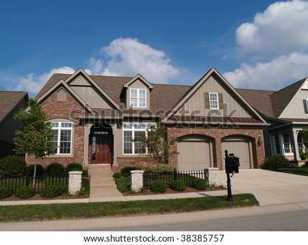 Small home with double garage in a neighborhood where the houses are built close together with very little yard. - stock photo