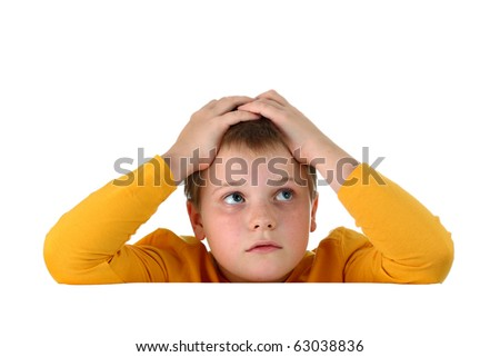 Small hopeless boy holding his head with both hands resting arms on blank whiteboard isolated on white