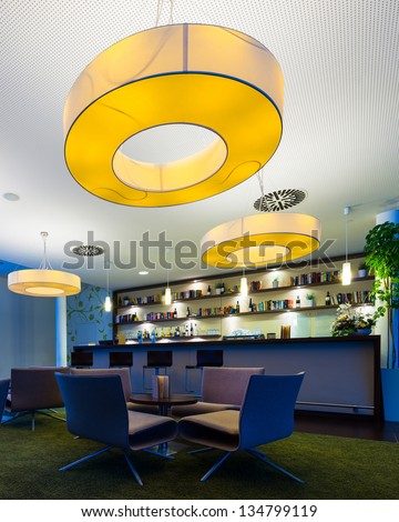 small hotel bar with huge lamps and bottle shelf - stock photo