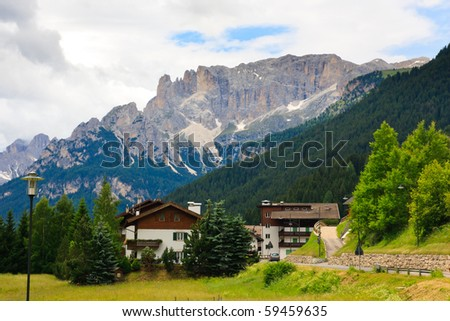 Small hotels, village road  and Dolomites view. - stock photo