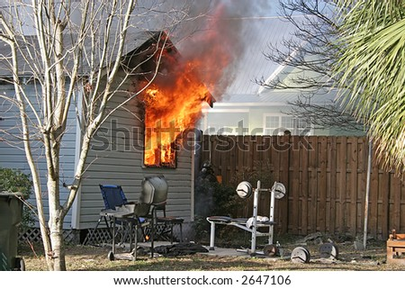 Small house ablaze with fire blowing through windows - stock photo