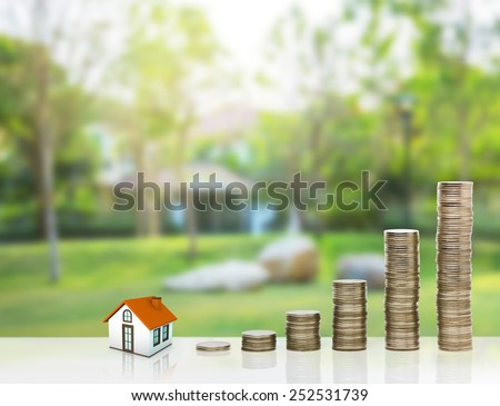 Small house and gold stack coins. The concept of purchase of habitation - stock photo