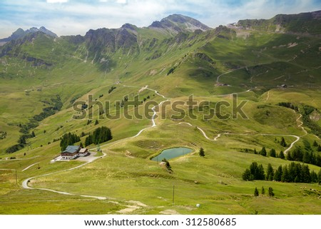 Small house and lake on mountain meadow in summertime - stock photo