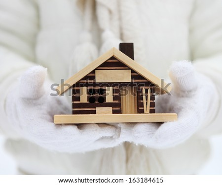 Small house in hands of a child. Winter - stock photo