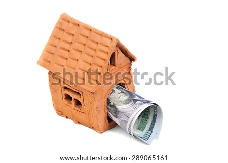 small house made of clay and money - stock photo