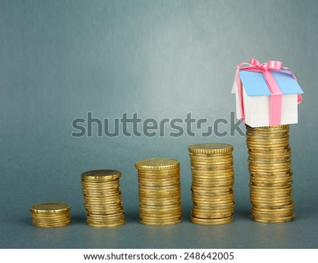 Small house standing on stack of coins on gray background - stock photo