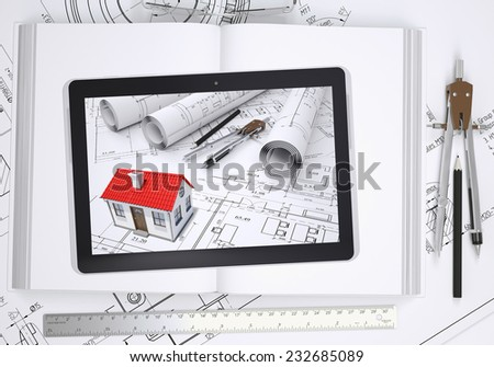 Small house with drawings displayed on tablet screen. Under the tablet lying open book and drawings with tools of architect. Construction concept - stock photo