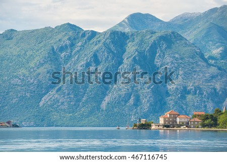 Small houses on the water and mountains on the background with soft focus in the bay of Kotor in Montenegro