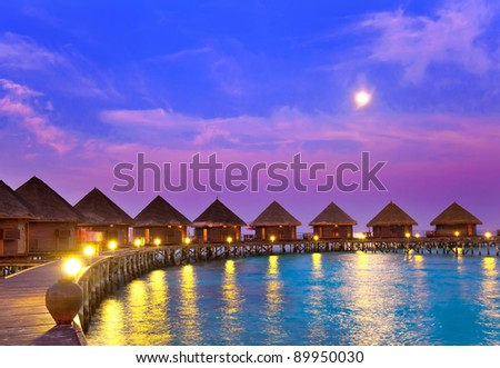 small houses on water on a sunset - stock photo