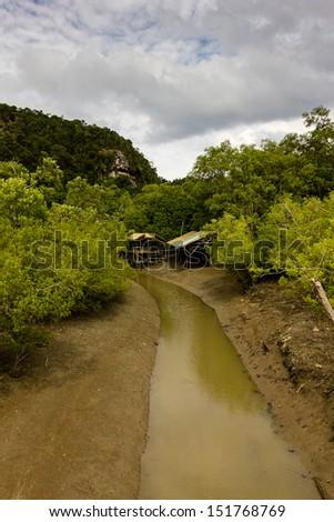 Small huts near a river in the jungle - stock photo