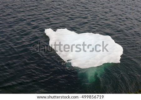 Small iceberg floating on surface of Atlantic Ocean water slowly melting away