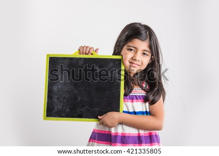 small indian girl holding and presenting blank school slate board in both hands, asian girl with school slate board, isolated over white background - stock photo