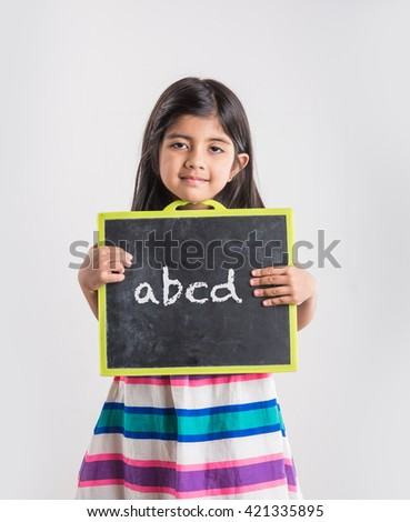 small indian girl holding school slate board and abcd written with chalk, girl education in india concept, asian girl and school slate board - stock photo