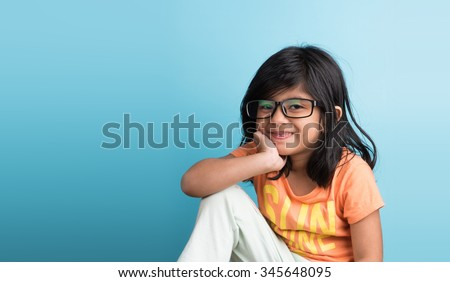 small indian girl with glasses, closeup on blue background, asian girl, 4 year indian girl, smiling, cute look, studious,black hair, long black hair, front view,passport photo, hand on chik - stock photo