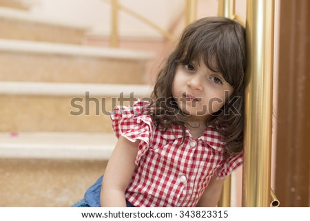 Small Iraqi girl sitting on marble stair inside house  - stock photo