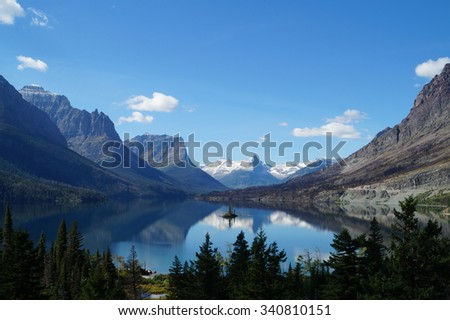 Small island in a lake between the mountains in Glacier National Park. The water is like a mirror reflecting the surroundings. - stock photo