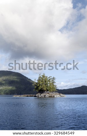 Small island in British Columbia's Inland Passage in summer with a cloud. - stock photo