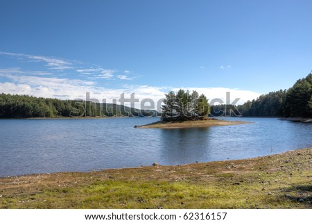 small island in cove on lake - stock photo
